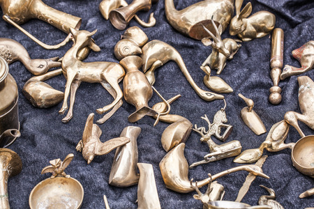 oldie: closeup of display of old brass objects in shape of miniature animals such as deer,bird,duck,camel for decoration or collection sold at flea market or garage sale for antique collection Stock Photo