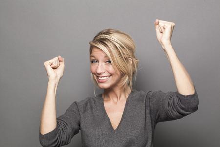 succes concept - gelukkige jonge blonde vrouw het winnen van een wedstrijd met leuke lichaamstaal en handen omhoog Stockfoto