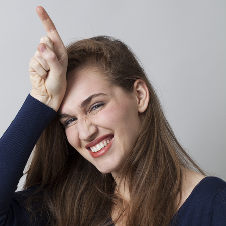 l hand: beautiful young woman making the L sign on forehead for loser message, cool hand gesture for youth culture, toothy smile