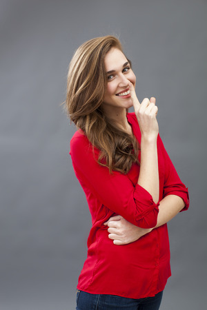 discretion: fun secret concept - beautiful 20s woman wearing red shirt smiling in showing a finger on her lips for discretion,profile view,studio shot