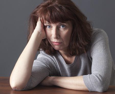 depressief volwassen vrouw die haar gezicht op haar handen vaststelling op een tafel voor luiheid of frustratie