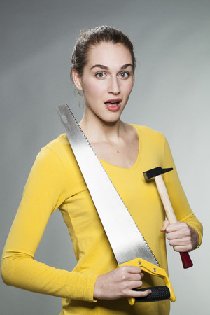 handiwork: female DIY concept - amazed beautiful young woman holding saw and hammer to prove her home handiwork expertise Stock Photo