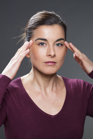 acupressure hands: focused 30s woman practising face acupressure with hands on face and temples for natural eye care or anti-migraine massage
