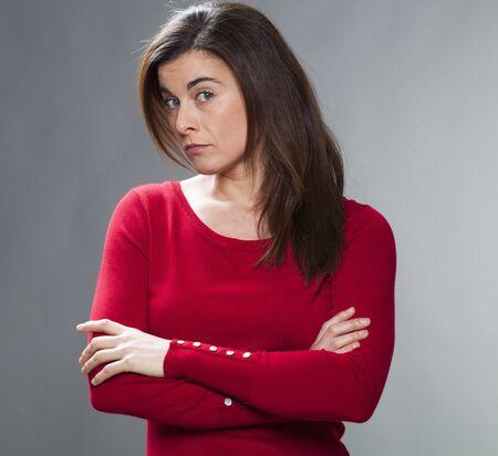 interrogativa: mujer joven interrogativa con el pelo marr�n y su�ter rojo con los brazos cruzados, girando la cabeza para escuchar la pregunta y la informaci�n
