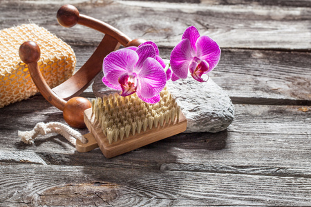 indulging: spa beauty treatment concept - symbols of nail care, massage and hygiene for indulging yourself set on old wood, gray texture stone and pink orchid flower background for genuine body care decor