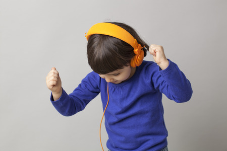 playing music: smiling infant with headphones focusing on rhythm and music