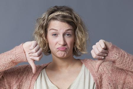 decepci�n: concepto decepci�n - decepcionado mujer joven con el pelo rubio rizado haciendo doble pulgares hacia abajo con la cara divertida para el desaliento y la infelicidad