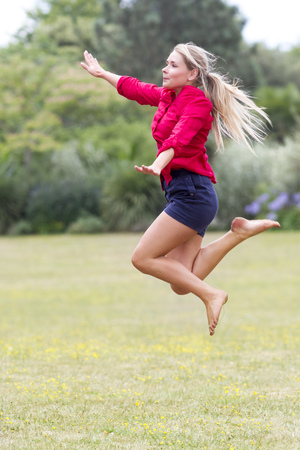suntanned: celebrating success outdoors concept - excited beautiful young woman in shorts jumping high with arms raised for freedom and happiness in city park,natural summer daylight