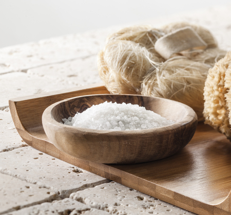 exfoliation: Spa and beauty concept - loofah and bath salt for body cleansing and exfoliation mineral set on beige background atmosphere for relaxation Stock Photo