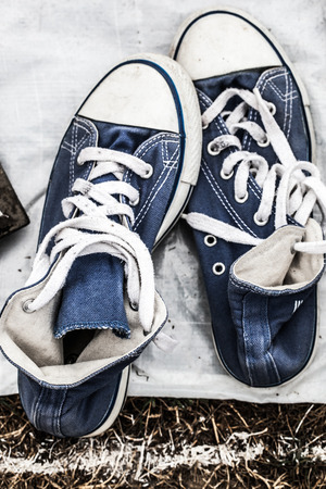 reusing: second hand fabric navy blue sneakers on sale at garage sale on grass for donation, recycling or selling for cheap to cope with over-consumption and fashion