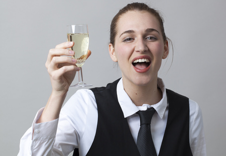 bubbly: drunk young woman wearing uniform of wine waitress raising bubbly wine in glass of Champagne Stock Photo