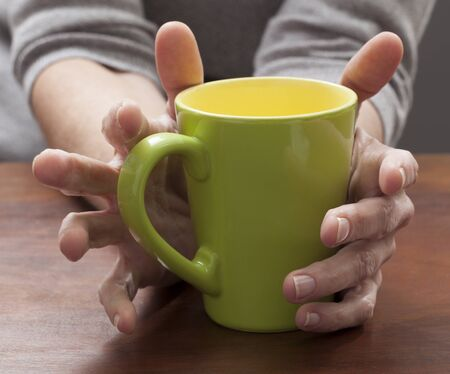 women holding cup: closeup on female hands thinking and holding a coffee mug at home