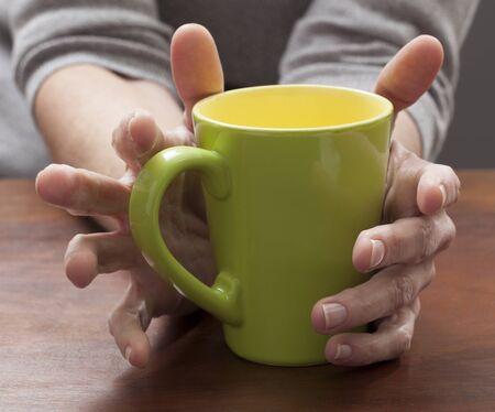 taza: portarretrato en manos femeninas pensando y sosteniendo una taza de caf� en el pa�s Foto de archivo