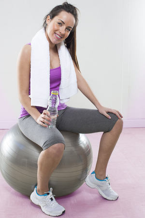 20s: 20s athletic woman sitting on a pilates ball with bottle of water after her fitness exercise