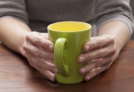 tea breaks: close-up on mature womans hands thinking and relaxing at breaks with a green cup of coffee or tea Stock Photo