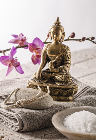 inner beauty: pedicure pumice and concept with pampering bath salt and spiritual Buddha background Stock Photo