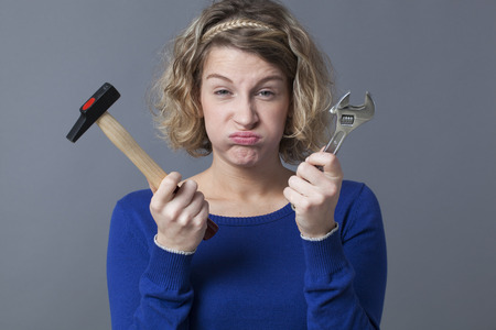 manual work: female DIY concept - puffing young blond woman unhappy at holding spanner and hammer as symbols of manual work and mechanics handiwork Stock Photo