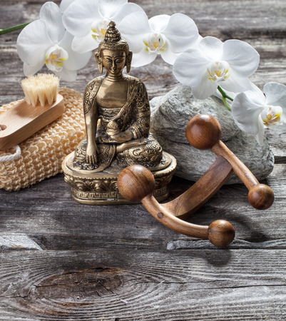 inner beauty: spa beauty treatment concept - symbol of massage and exfoliation for inner beauty with Buddha on old wood, gray texture stones and white orchid flower background for genuine feng shui decor