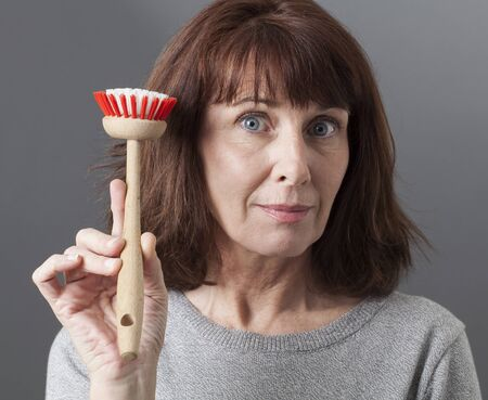 handing over: smiling mature woman with dish brush in hand as housekeeping queen or mother handing over washing dishes tool