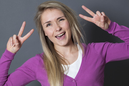 ecstatic: success concept - ecstatic young blonde girl showing a double victory sign for achievement