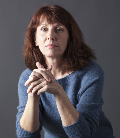 portrait of mature woman with brown hair and blue winter sweater thinking,hands together,looking calm and thoughtful