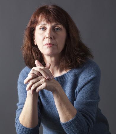 Portret van rijpe vrouw met bruin haar en blauwe winter trui denken, handen, op zoek naar rust en doordachte