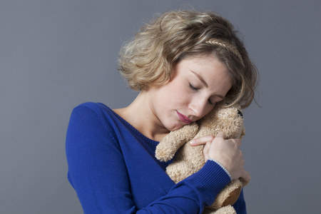 warmth: sleepy young blonde woman hugging her teddy bear tightly with tenderness for cozy warmth