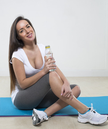 gym clothes: thirsty young fitness woman sitting on an exercise mat with gym clothes and bottle of water
