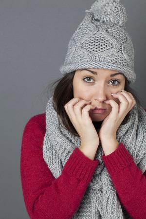 decepci�n: concepto decepci�n - retrato de una mujer de 20 a�os con el triste invierno sombrero gris y bufanda del invierno expresando su decepci�n con las manos y la cara expresiva, tiro del estudio