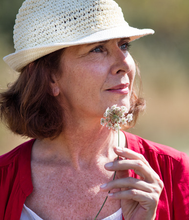 wellbeing in countryside - closeup of gorgeous mature woman with summer hat thinking,alone with field flower in hands,natural summer daylight