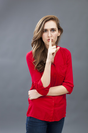 taboo: secret and taboo concept - unhappy 20s woman wearing red shirt asking for silence with finger on mouth,studio shot Stock Photo