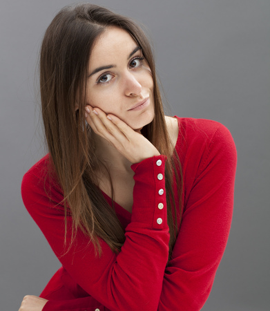 dubious: dubious young girl with long brown hair and smart red sweater leaning her head on hand for thought
