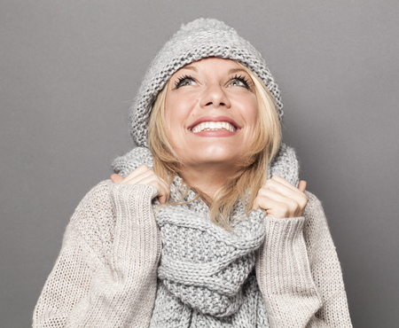 sexiness: cheeky young woman with blonde hair wearing winter hat and clothes, looking up for fun and sexiness Stock Photo