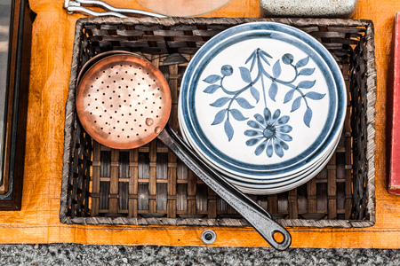 second hand: display of second hand brass kitchen utensil and 60s or 70s flowery plates in rattan tray for reusing or recycling sold at garage sale for vintage collection Stock Photo