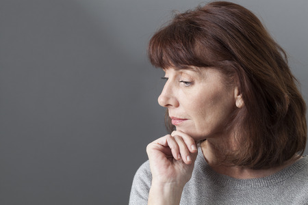 affective: thinking mature woman with brown hair and grey sweater on profile,looking serene or with SAD syndrome,copy space Stock Photo