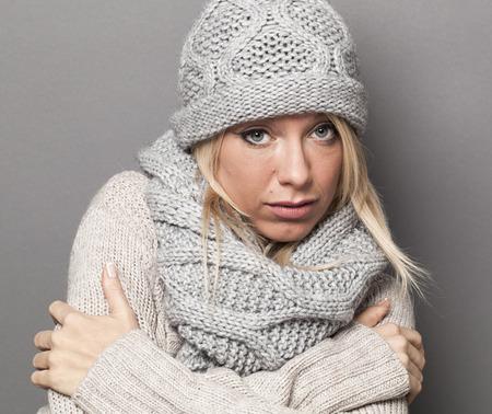 trendy warm winter - traurig junge, blonde Frau, die versucht, warm zu bleiben in Einwickeln sich in grauer Wolle Wintermütze und Schal für Komfort und gemütliche Temperatur