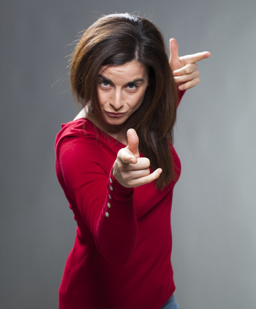 criticize: focused brunette woman staring at someone with index finger and torso forward accusing and patronizing someone with fun and self-assurance Stock Photo