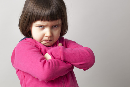 arms crossed: unhappy boyish 4-year old girl expressing disagreement with body language Stock Photo