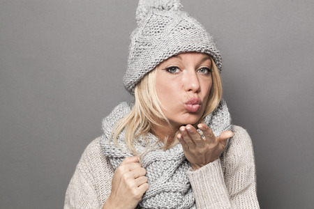 extrovert: love and happiness concept - fashionable winter young blond girl wearing gray wool sweater and warm scarf sending kisses for valentines,studio shot