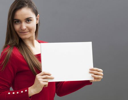 teasing: seductive young woman wearing red holding a copy space communication board with teasing news on Stock Photo