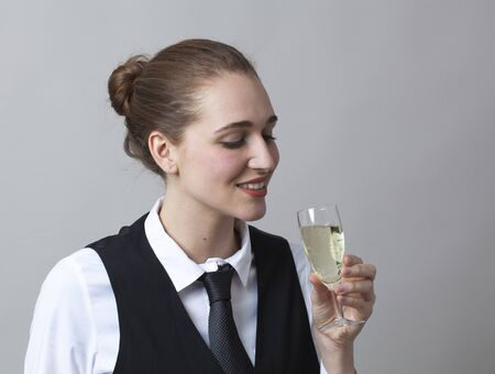 bubbly: Beautiful young woman wearing uniform of wine waitress tasting a bubbly wine in glass of Champagne