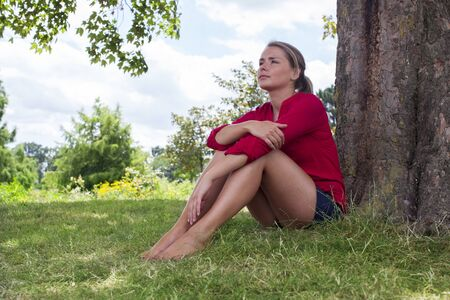 suntanned: reflection tree concept - beautiful young suntanned blond woman resting in the grass in the shade for relaxation, natural daylight summer, low wide angle view Stock Photo