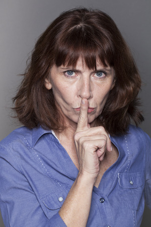 taboo: secret and taboo concept - judge mental 50s woman wearing blue shirt asking for silence with finger on lips,studio shot