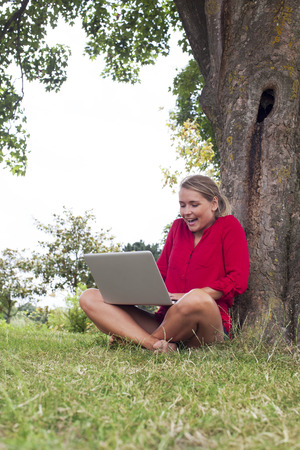 suntanned: working outdoors - beautiful suntanned 20s girl enjoying working with laptop on crossed legs sitting under tree as freelancer,natural summer daylight