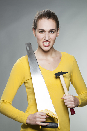 prove: female DIY concept - self-assured beautiful young woman holding saw and hammer to prove her home improvement expertise Stock Photo