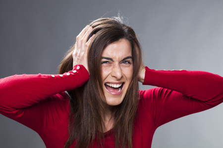unbearable: raging young woman having painful headache, covering closed ears, annoyed by noisy music, ignoring someone, not wanting to hear their side of story Stock Photo