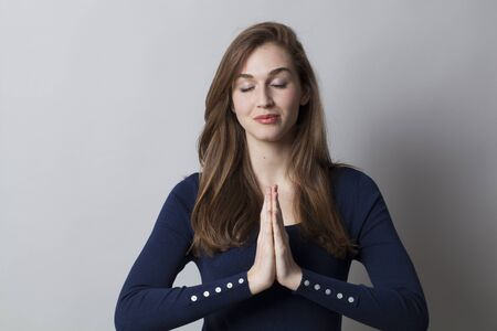 closing eyes: meditation concept - zen smiling young woman wearing a smart navy blue sweater holding hands together,closing eyes for relaxation