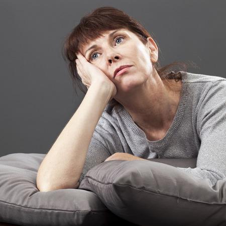 mujeres maduras: renunci� mujer mayor que se reclina la cara y las manos que se establecen en cojines para mayor comodidad al tener problemas de salud