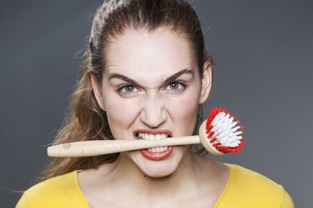obsessive: young gorgeous woman biting dish brush for housekeeping rebellion and strong disagreement