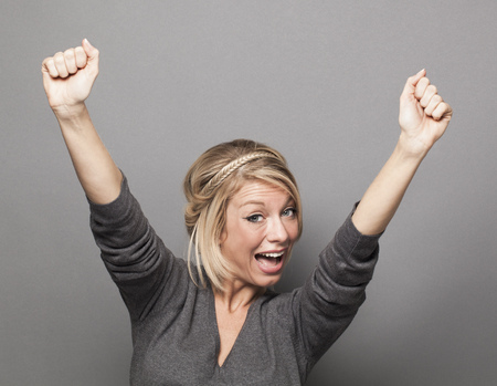 extrovert: success concept - sexy young blonde woman winning a competition with fun body language and hands up above